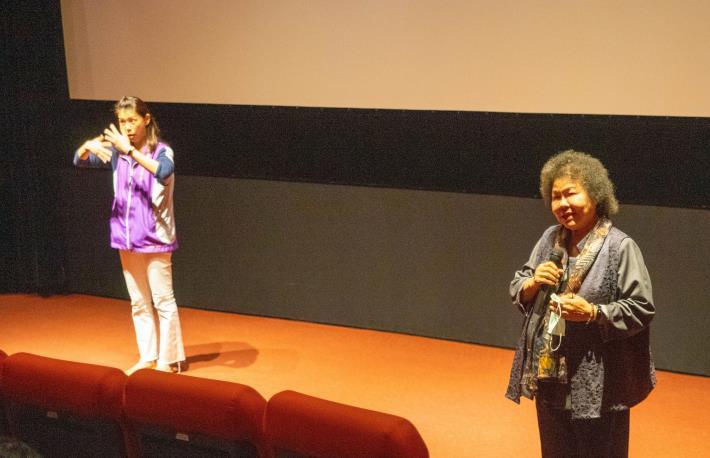 國家人權委員會11日晚間邀身障團體包場電影〈無聲〉,主委陳菊(右)致詞時,特別安排手語老師(左)協助翻譯,並且特別補光讓聽障朋友看得更清楚