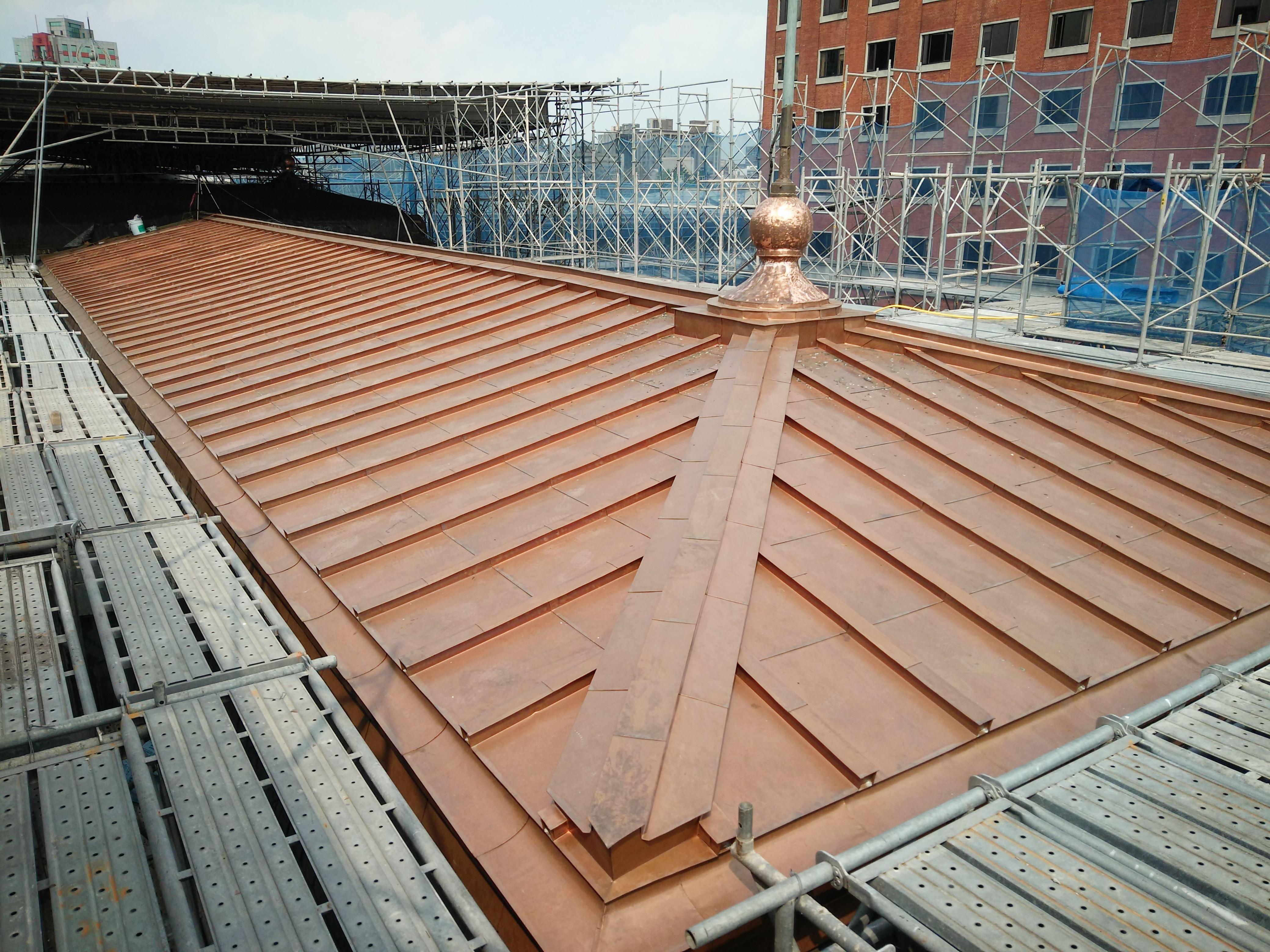 銅瓦匠師逐片按區域形狀加以裁剪安裝,漸次完成屋面細部收邊